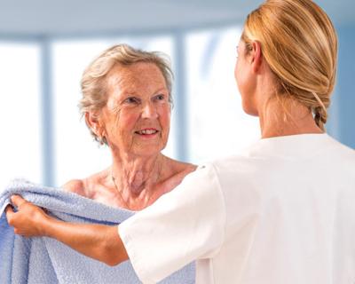 a caregiver giving a senior woman a towel