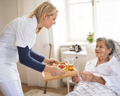 a caregiver giving meal to a senior woman in bed